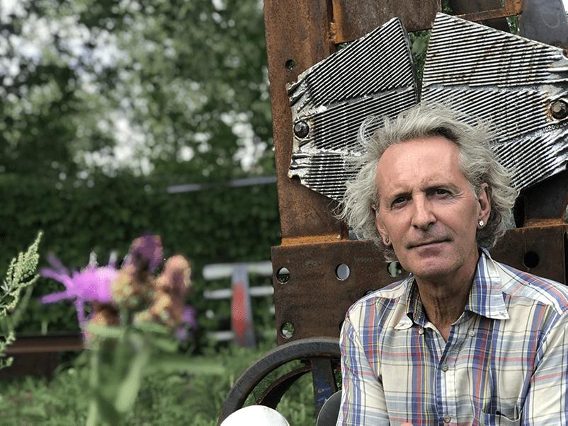 Glen LeMesurier qui se tient devant une de ses oeuvre en fer recyclé