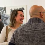 Femme souriante au travers d'autres personnes dans une pièce remplie de gens