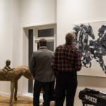 Deux hommes observent une peinture en noir et blanc