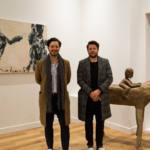 Deux hommes posent devant une sculpture en bois dans un appartement