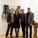 Trois hommes et une femme posent devant un tableau en noir et blanc