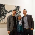 Deux hommes et une femme posent devant un tableau en noir et blanc