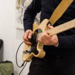 Gros plan sur la guitare du musicien, qui joue de son ihnstrument.
