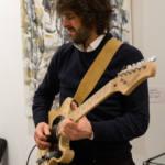 Un musicien joue de la guitare électrique durant une soirée.