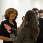 Deux femmes discutent dans une pièce bondée de gens.